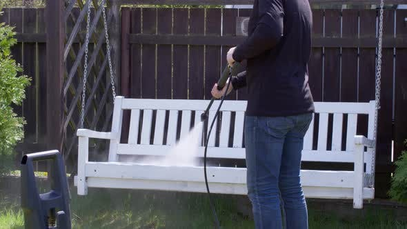 Thumbnail for Caucasian Gardener Is Cleaning Chain Hanging Bench Using High Pressure Washer