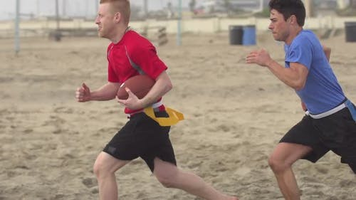 A group of guys playing flag football on the beach.