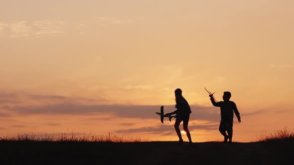 Thumbnail for Silhouettes of a Girl and a Boy Playing Together with Airplanes at Sunset. A Happy and Carefree