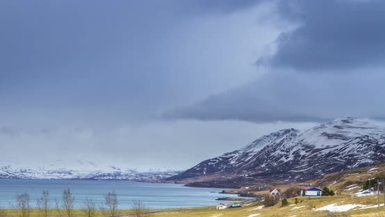 Cloud rolling time lapse over snow mountain fjords in Akureyri, Iceland.
