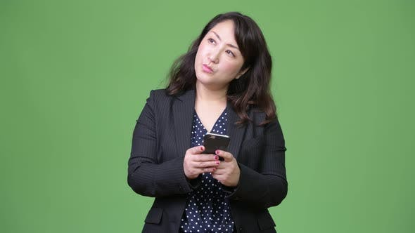 Thumbnail for Mature Beautiful Asian Businesswoman Thinking While Using Phone
