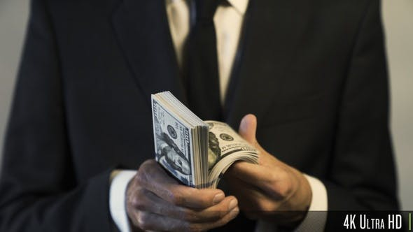 4K Businessman Holding and Counting American $100 Dollar Banknotes for Money and Financial Concept