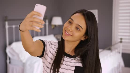 Thumbnail for A cute teen takes a selfie in her bedroom