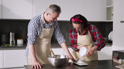 Couple Cooking Together Woman Measuring Sugar Portion