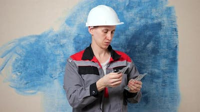 Focused Handyman Wearing Jumpsuit Counts Money in Apartment