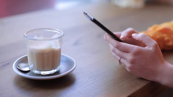 Woman Hands Using Smart Phone Sitting in a Cafe