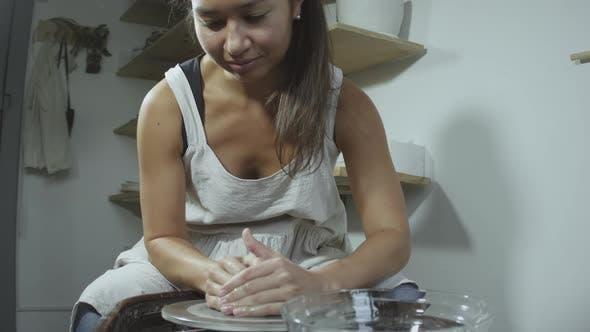 Thumbnail for Asian potter works on potter's wheel in studio