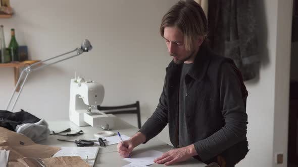 Male Tailor Draws Creative Sketch of Clothes in Workshop