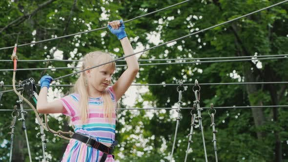 Thumbnail for A Brave Girl Moves Along the Ropes Between the Trees, Uses a Safety Rope