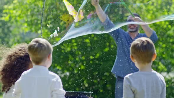Thumbnail for Man Launching Giant Bubble Up in the Air at Kids Party