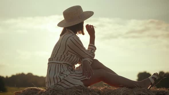 woman in hat resting on a haystack on a sunset background