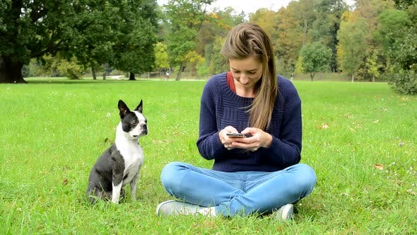 Thumbnail for Young Attractive Happy Woman Writes Messages on the Smartphone and Ignores Her French Bulldog
