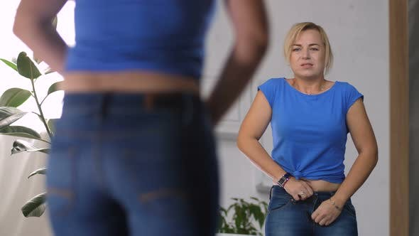 Thumbnail for Adult Woman Struggling To Zip Up Too Tight Jeans