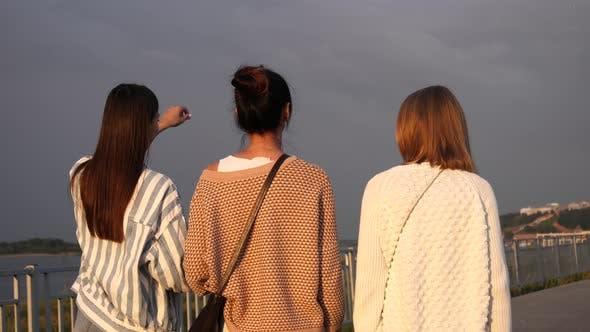 Thumbnail for Gruppe junger Damen Wandern und Chatten entlang der Promenade.
