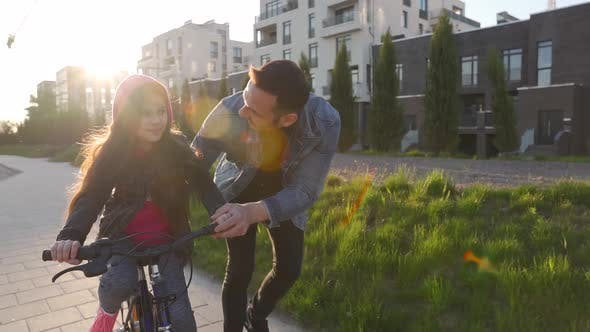 Thumbnail for Dad Is Teaching Daughter How To Ride Bicycle at Sunset