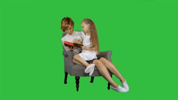 Thumbnail for Mother and Daughter Sitting and Reading Book Together On