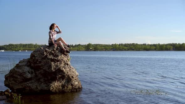 Thumbnail for A Young Woman Sits on a Stone By the River and Admires Nature. Girl in Nature.