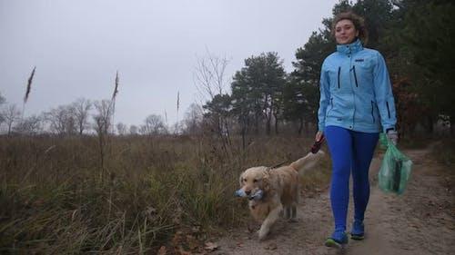 Labrador Retriever Helping Woman Picking Up Litter
