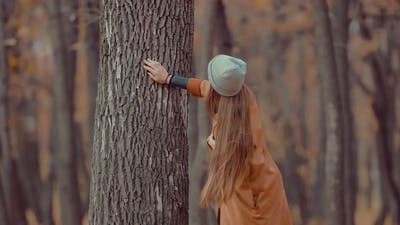 Woman Looks at the Top Near the Tree and is Looking for Something