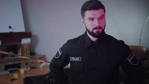 Porträt von gutaussehenden kaukasischen bärtigen Polizeibeamten stehend am Tatort und Denken