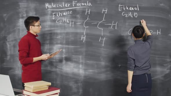 Thumbnail for Teacher Watching Student Writing Chemical Formula on Chalkboard