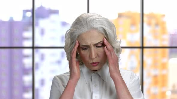 Old Lady with Headache Massaging Her Temples