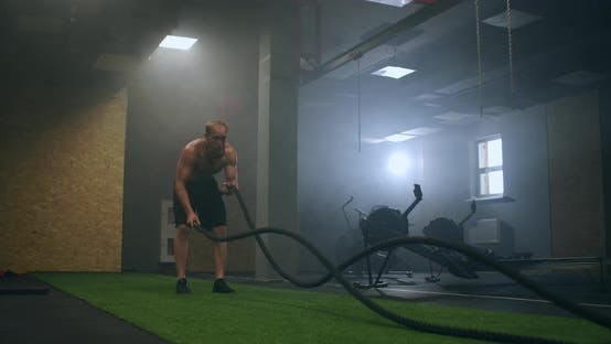Thumbnail for Fitness Man Exercising with Battle Rope Abandoned Warehouse. Tough Man Working Out in Cross Training