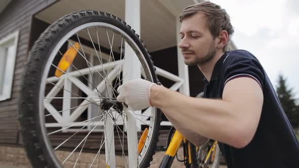 Young bearded man repairing his broken bicycle