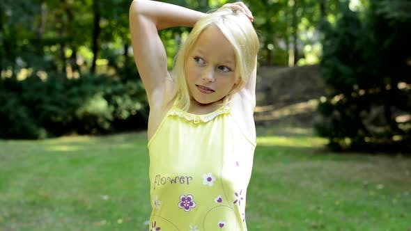 Thumbnail for Little Lively Girl Stretchs Her Arms and Neck in the Park - Workout