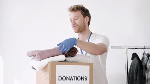 Young Volunteer Checking Clothes Donation Box and Making Notes Humanitarian Aid