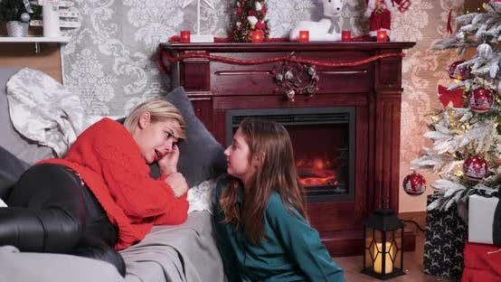 Thumbnail for Mother Lying on Sofa Smiling After Her Little Daughter Gave Her a Christmas Gift