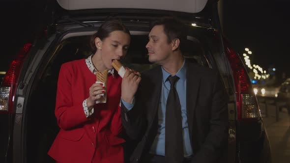 Thumbnail for Business Colleagues Sharing Meal in Car at Night