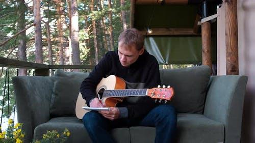 Man Playing Guitar and Writing Lyrics for Song