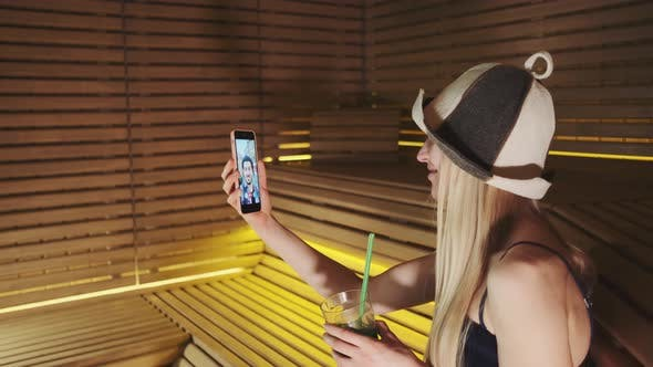 Profile View of Woman in Sauna Speaking with Friend By Video Call