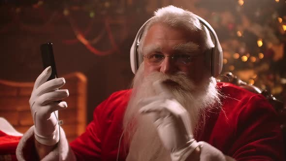 Thumbnail for Modern Santa Claus Is Listening To Christmas Song By Headphones and Smartphone, Portrait of Wizard