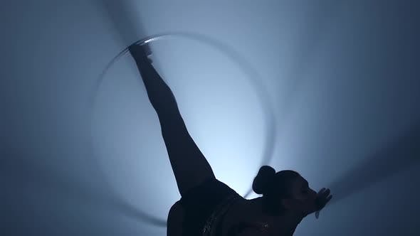 Thumbnail for Gymnast Turns the Metal Hoop on the Arm Then on the Leg. Smoke Background. Slow Motion