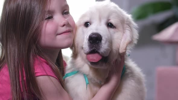 Thumbnail for Portrait of Sweet Little Girl Cuddling with Puppy