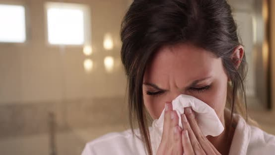 Thumbnail for Sick Caucasian woman blowing nose into tissue paper in clean bathroom setting