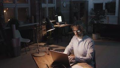 Man Working In Dark Empty Office Alone