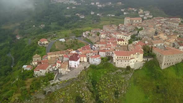 Cover Image for Aerial View Drone Flies Over Medieval Village on Hill Overlooking Misty Mountain Gorge