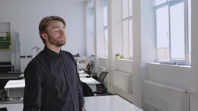 Bearded Man Stands and Look on the Window