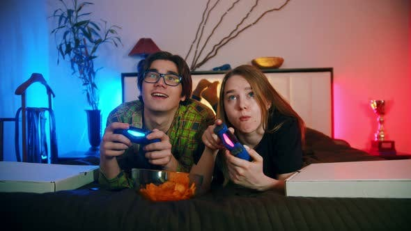 Thumbnail for Girlfriend and Boyfriend Playing Video Games in Their Bedroom