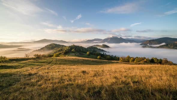 Thumbnail for Foggy Morning Sunrise with Clouds Moving over Beautiful Country in Mountains
