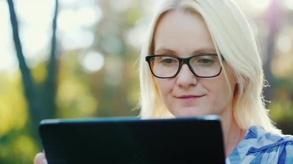 Thumbnail for Portrait of a Young Woman Wearing Glasses, Enjoying a Tablet