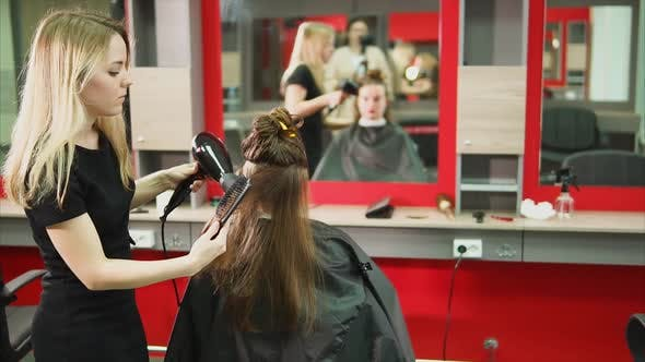 A Hair Stylist Combs the Client Hair Salon with a Hair Drier and a Hair Comb
