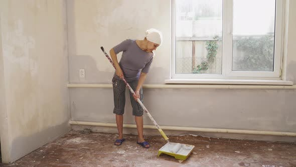 Woman Painter Paints Wall Indoors By Paint Roller And Paint.