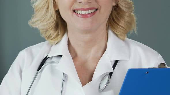 Thumbnail for Experienced Physician with Stethoscope Holding Folder and Smiling Into Camera