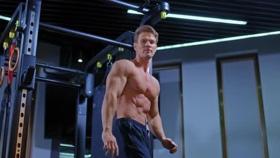 Hübscher männlicher Bodybuilder trainiert im Fitnessstudio und posiert mit Körpermuskeln. Gepumpte Muskeln von