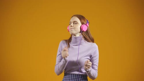 Beautiful Redhaired Young Woman Dances and Sings to Music She Listens to Music with Headphones on an
