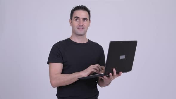 Cover Image for Happy Handsome Man Thinking While Using Laptop